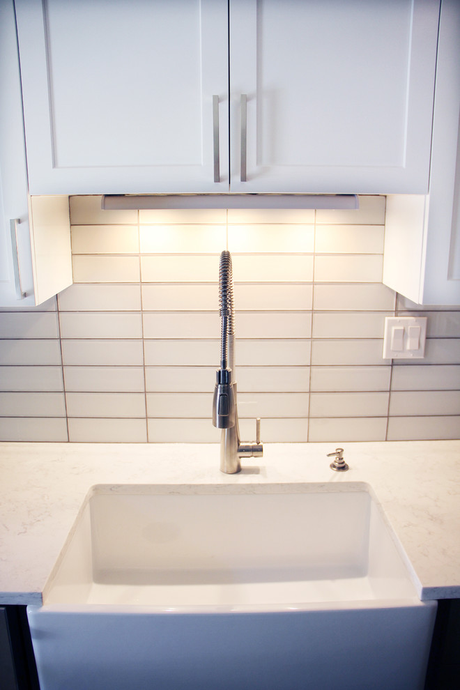Small minimalist galley medium tone wood floor and brown floor eat-in kitchen photo in Portland with an undermount sink, shaker cabinets, white cabinets, marble countertops, white backsplash, subway tile backsplash, stainless steel appliances and no island