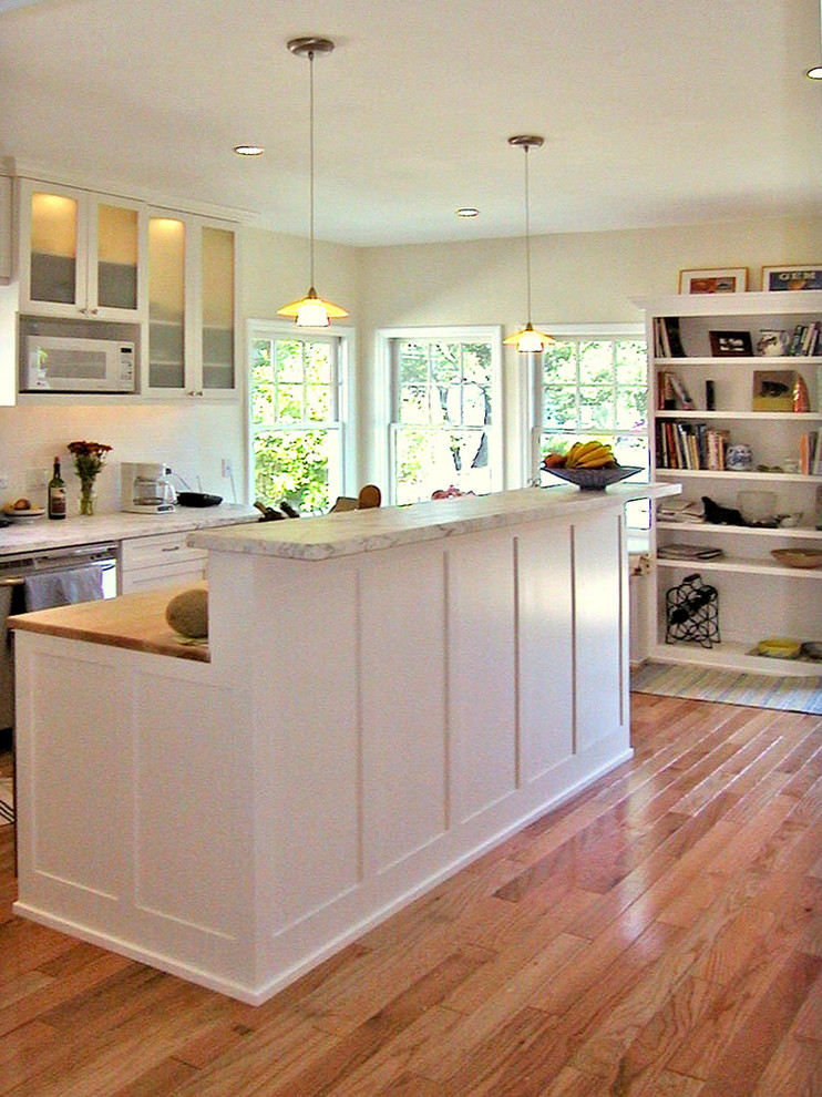 Example of a mid-sized classic u-shaped light wood floor kitchen design in San Francisco with shaker cabinets, white cabinets, marble countertops, white backsplash, subway tile backsplash, stainless steel appliances and an island