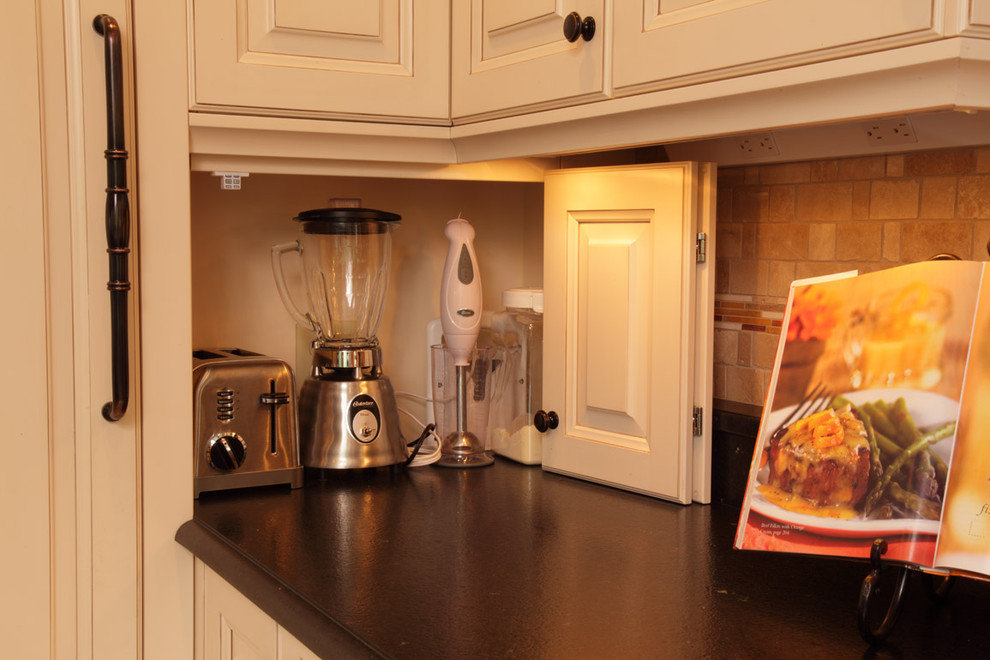 Elegant kitchen photo in Minneapolis with black countertops