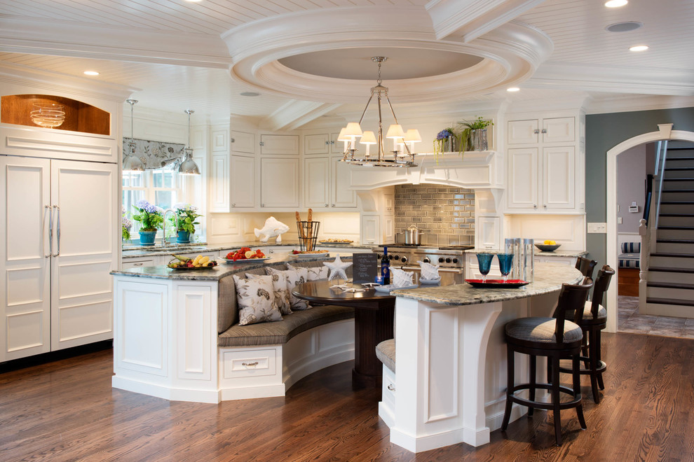Example of a large classic l-shaped dark wood floor open concept kitchen design in Charleston with an undermount sink, beaded inset cabinets, white cabinets, granite countertops, gray backsplash, paneled appliances, two islands and wood backsplash