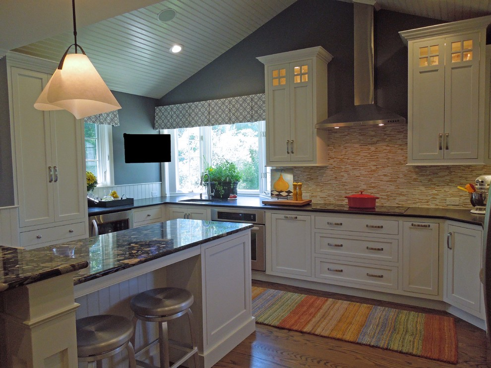 Inspiration for a timeless u-shaped medium tone wood floor eat-in kitchen remodel in Boston with an undermount sink, beaded inset cabinets, white cabinets, granite countertops, multicolored backsplash, stainless steel appliances and an island