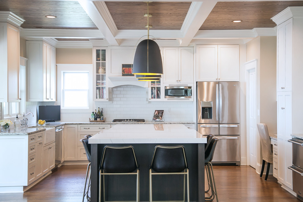 Inspiration for a large transitional u-shaped medium tone wood floor and brown floor enclosed kitchen remodel in Milwaukee with a farmhouse sink, quartz countertops, white backsplash, subway tile backsplash, stainless steel appliances, an island, white countertops, shaker cabinets and white cabinets