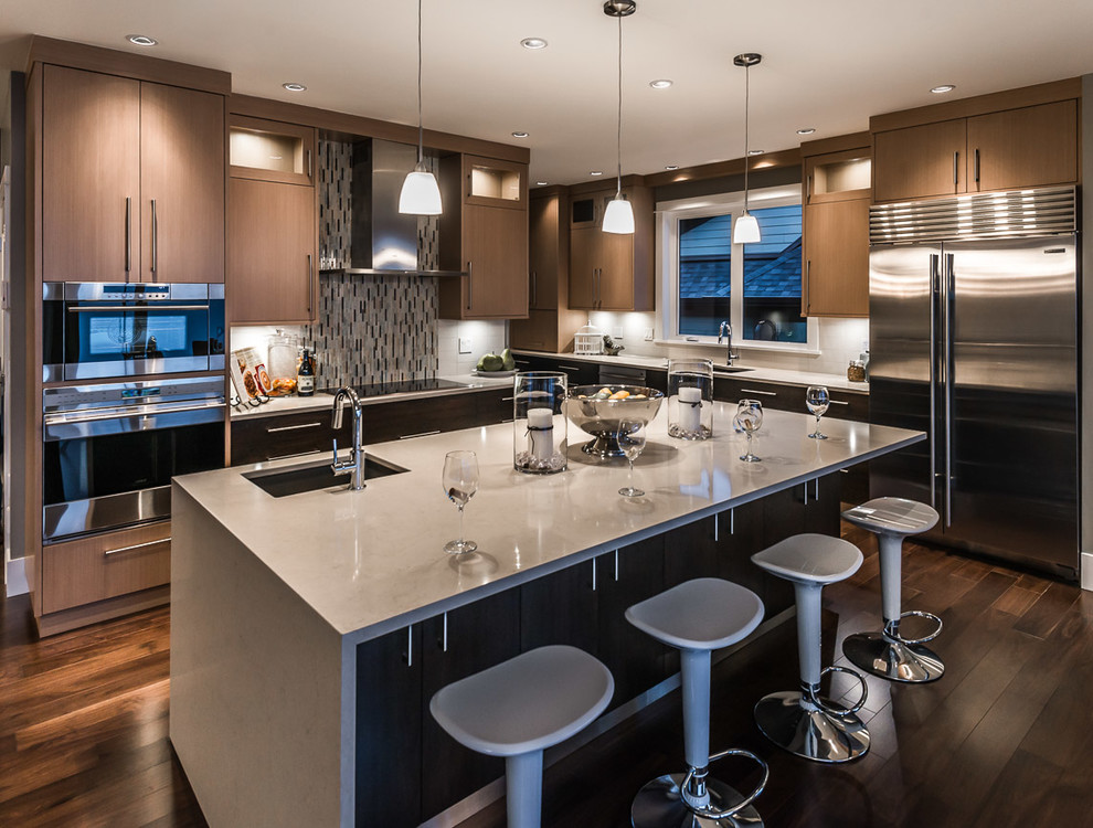 Trendy l-shaped kitchen photo in Vancouver with an undermount sink, flat-panel cabinets, dark wood cabinets, quartz countertops, stainless steel appliances and mosaic tile backsplash