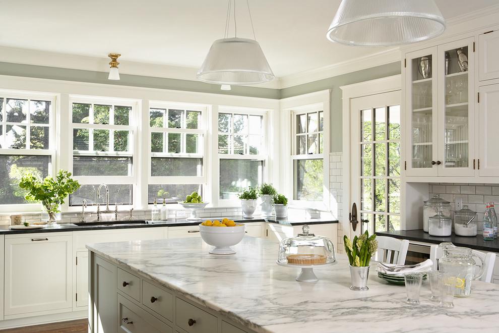 Elegant kitchen photo in Minneapolis with glass-front cabinets, white cabinets, white backsplash and subway tile backsplash