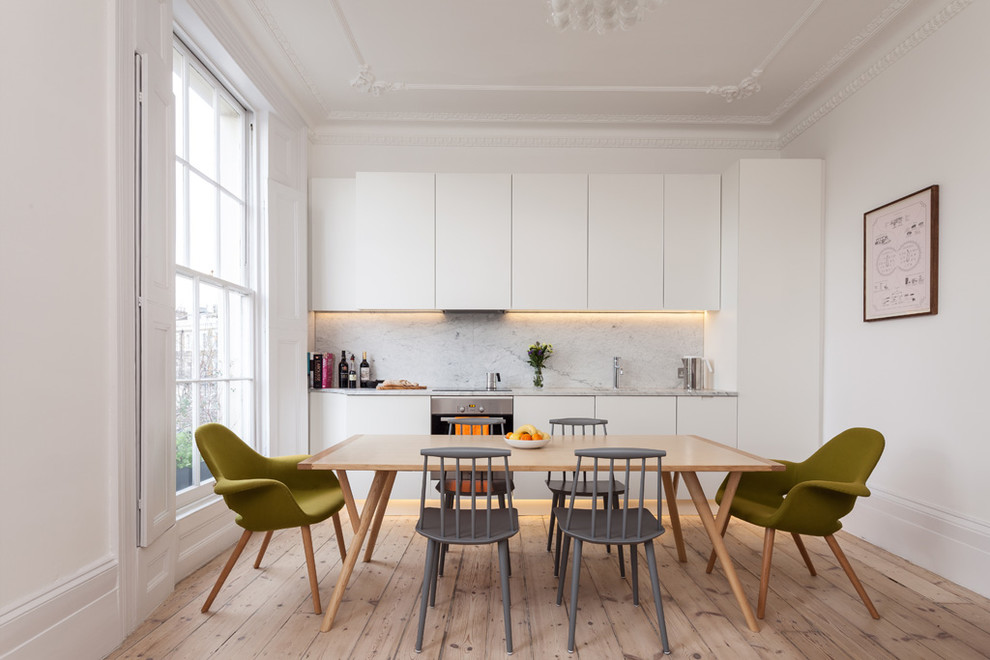 Example of a danish kitchen design in London with marble backsplash