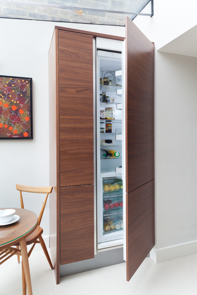 Kitchen - contemporary kitchen idea in London with flat-panel cabinets, paneled appliances and dark wood cabinets