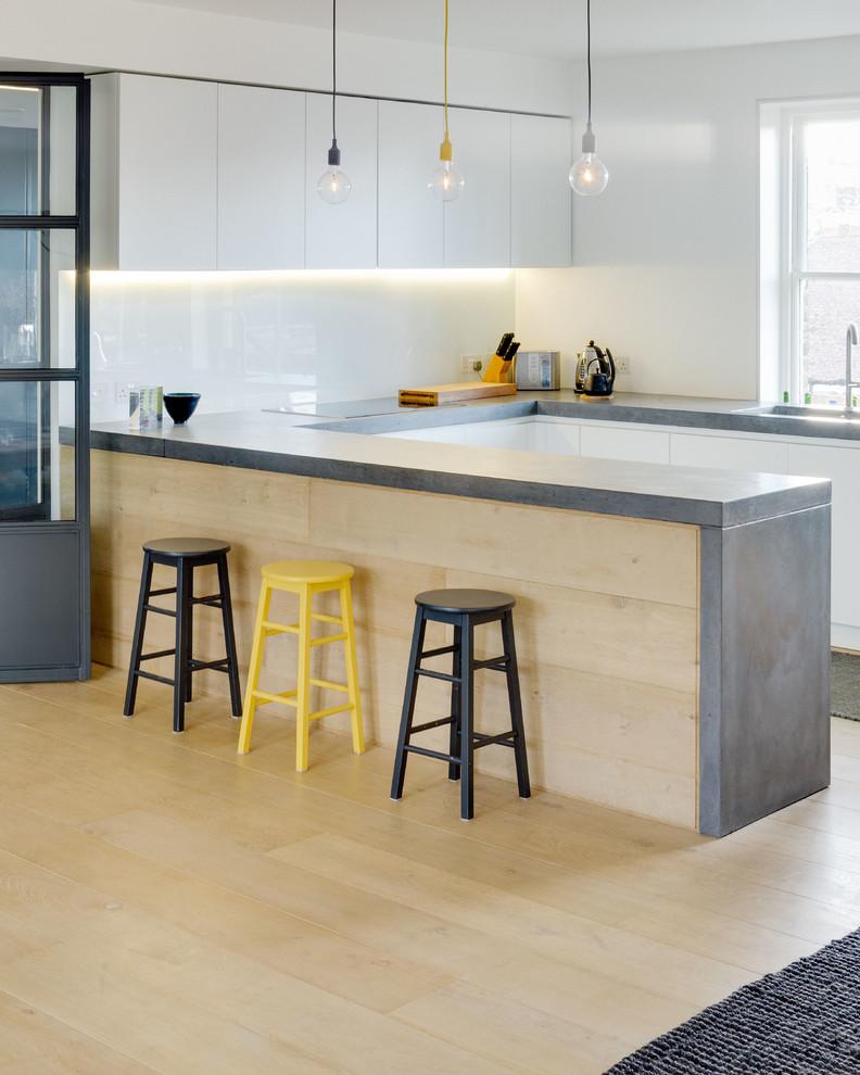Modelo de cocinas en U actual con armarios con paneles lisos, puertas de armario blancas, encimera de cemento, suelo de madera clara, península y suelo beige
