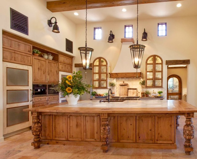 Inspiration for a large mediterranean l-shaped ceramic floor and beige floor eat-in kitchen remodel in San Diego with a farmhouse sink, beige backsplash, mosaic tile backsplash, stainless steel appliances, recessed-panel cabinets, medium tone wood cabinets, wood countertops and an island