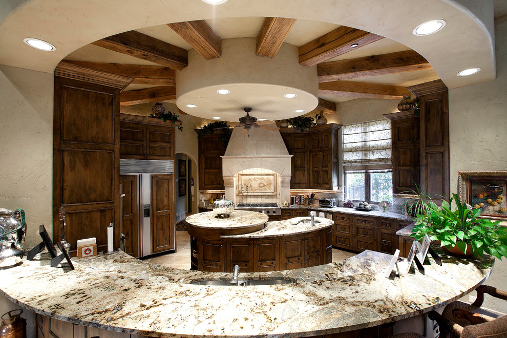Kitchen - mediterranean kitchen idea in Dallas with recessed-panel cabinets, dark wood cabinets and paneled appliances