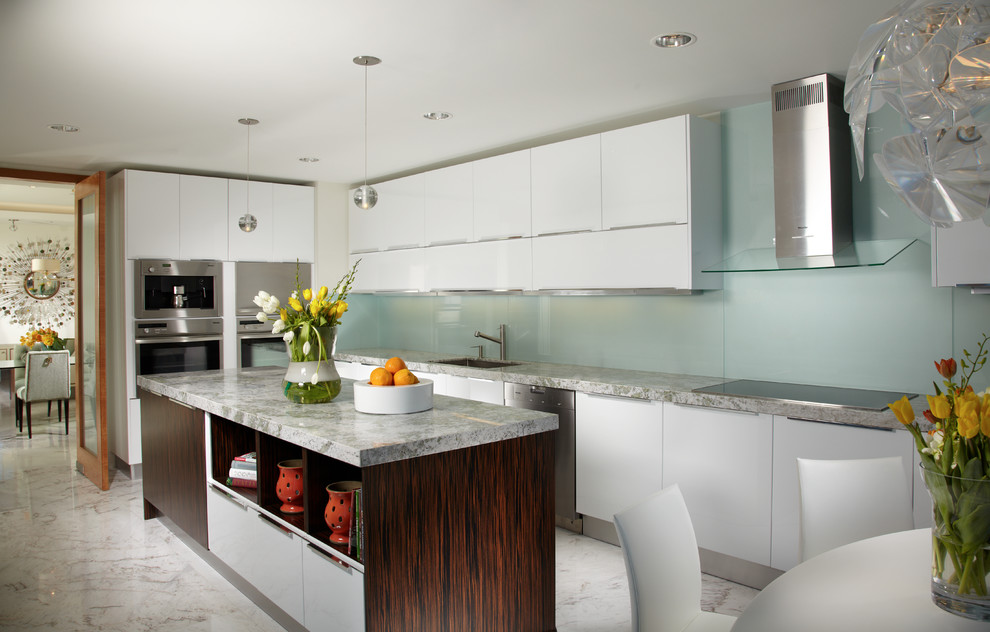Eat-in kitchen - large contemporary l-shaped marble floor and multicolored floor eat-in kitchen idea in Miami with flat-panel cabinets, glass sheet backsplash, white cabinets, stainless steel appliances, an undermount sink, marble countertops, green backsplash and an island
