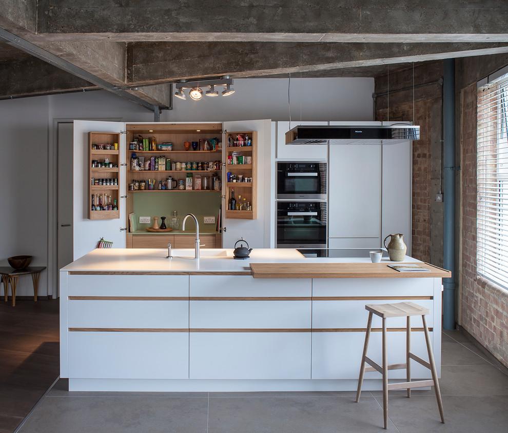 Modelo de cocina de galera, urbana, abierta, con puertas de armario blancas, encimera de acrílico, electrodomésticos negros, una isla, fregadero integrado y armarios con paneles lisos