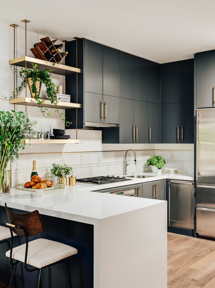 Inspiration for a contemporary u-shaped medium tone wood floor and brown floor kitchen remodel in San Francisco with an undermount sink, flat-panel cabinets, gray cabinets, quartz countertops, white backsplash, marble backsplash, stainless steel appliances, white countertops and a peninsula