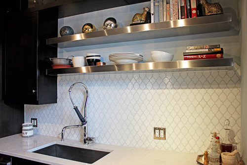 Stainless steel shelves were added above the kitchen sink to allow for the homeowners to display cookbooks and store additional cooking supplies.