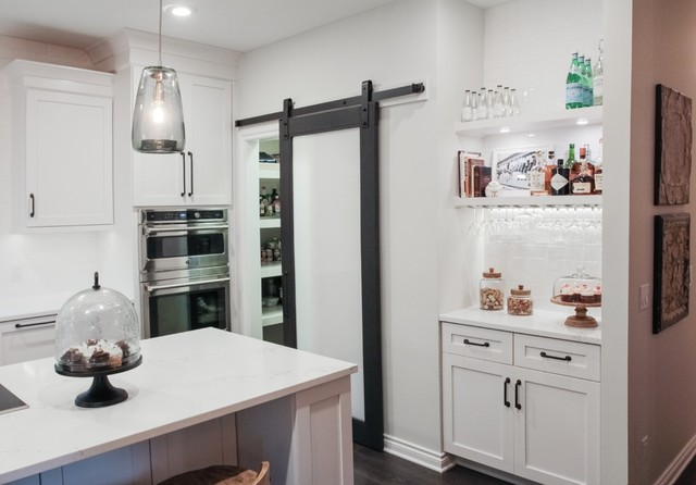 Example of a mid-sized transitional galley dark wood floor eat-in kitchen design in Grand Rapids with a farmhouse sink, shaker cabinets, white cabinets, quartz countertops, white backsplash, ceramic backsplash, stainless steel appliances and an island