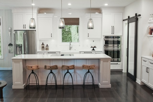Eat-in kitchen - mid-sized transitional galley dark wood floor eat-in kitchen idea in Grand Rapids with a farmhouse sink, shaker cabinets, white cabinets, quartz countertops, white backsplash, ceramic backsplash, stainless steel appliances and an island