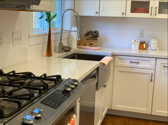 Eat-in kitchen - mid-sized rustic brown floor eat-in kitchen idea in Other with a farmhouse sink, raised-panel cabinets, white cabinets, quartz countertops, white backsplash, stainless steel appliances, an island and white countertops