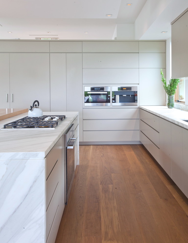 Example of a mid-sized 1960s l-shaped medium tone wood floor open concept kitchen design in Los Angeles with an undermount sink, flat-panel cabinets, gray cabinets, marble countertops, stainless steel appliances and an island