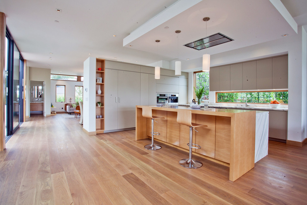 Example of a large mid-century modern u-shaped medium tone wood floor open concept kitchen design in Los Angeles with flat-panel cabinets, gray cabinets, marble countertops, stainless steel appliances and an island
