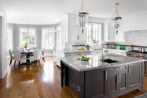 White ktichen remodel with a dark/black kitchen island with two massive glass pendant lights as a focal point.