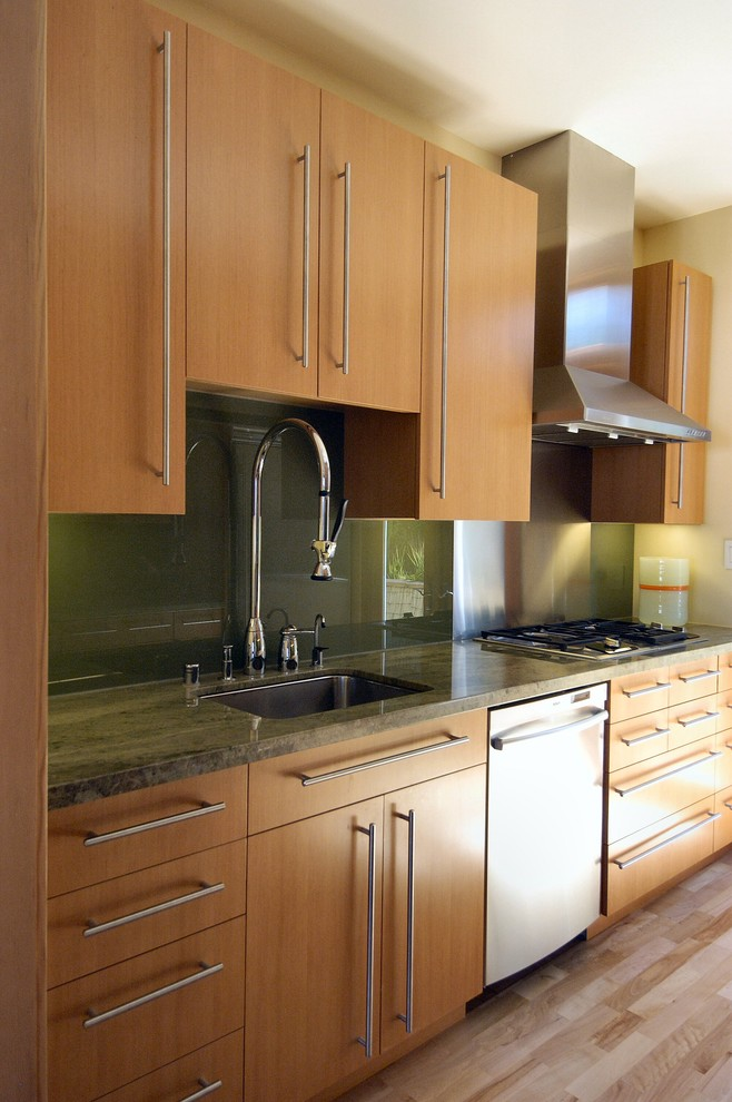 Example of an asian enclosed kitchen design in San Francisco with a single-bowl sink, flat-panel cabinets, light wood cabinets, granite countertops, green backsplash, glass sheet backsplash and stainless steel appliances