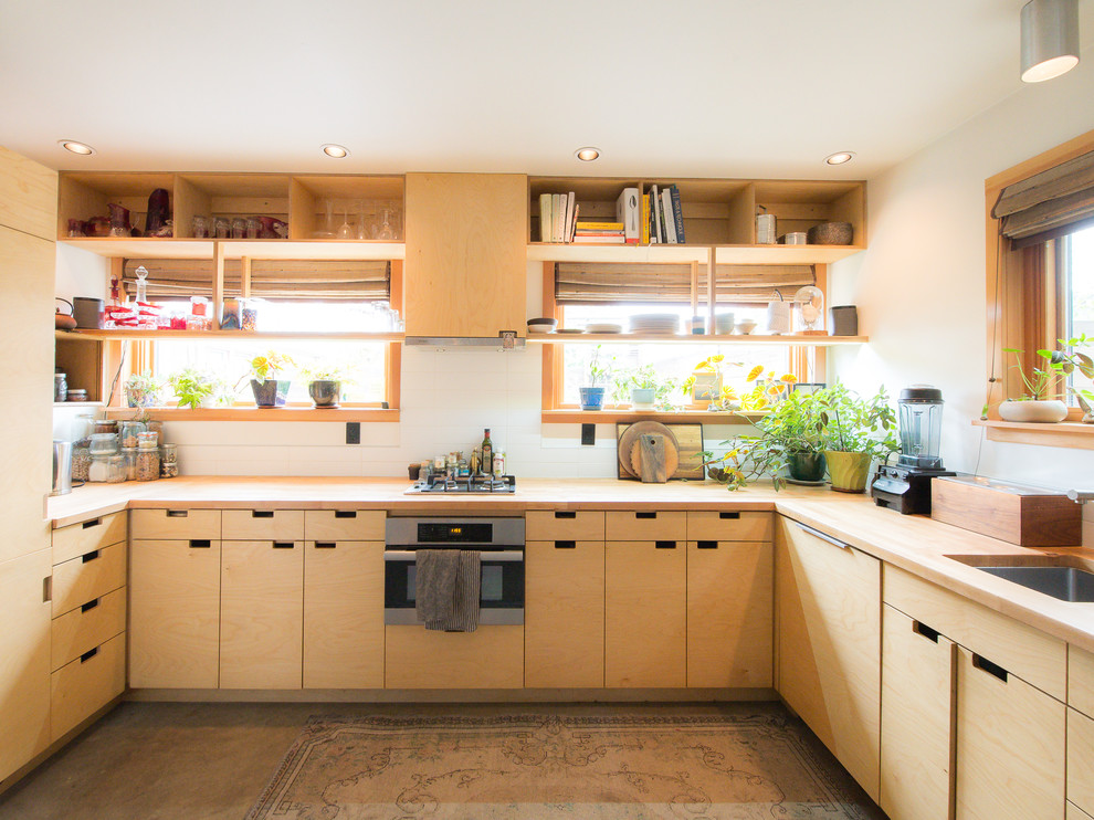 Example of an asian u-shaped concrete floor and gray floor kitchen design in Portland with an undermount sink, flat-panel cabinets, light wood cabinets, wood countertops, white backsplash, stainless steel appliances, no island and brown countertops