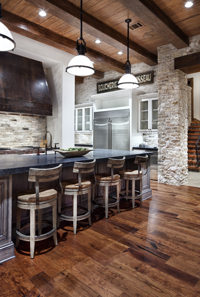 Tuscan kitchen photo in Other with glass-front cabinets and blue countertops