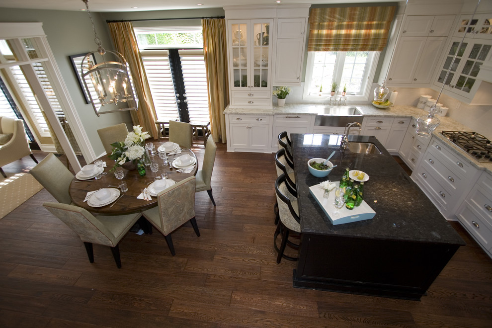 Eat-in kitchen - mid-sized contemporary u-shaped medium tone wood floor eat-in kitchen idea in Toronto with a farmhouse sink, shaker cabinets, white cabinets, marble countertops, white backsplash, ceramic backsplash, stainless steel appliances and an island