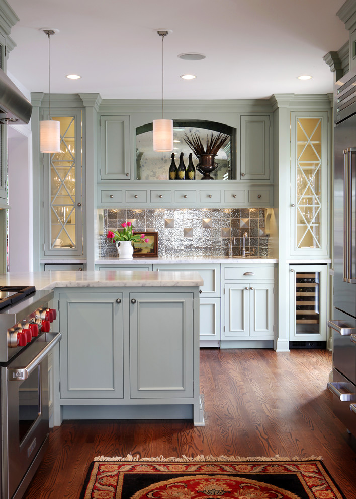 Example of a mid-sized classic u-shaped medium tone wood floor enclosed kitchen design in St Louis with stainless steel appliances, an undermount sink, recessed-panel cabinets, green cabinets, marble countertops, metallic backsplash and metal backsplash