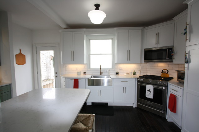 Inspiration for a mid-sized transitional l-shaped dark wood floor and brown floor eat-in kitchen remodel in New York with a farmhouse sink, shaker cabinets, white cabinets, quartz countertops, white backsplash, subway tile backsplash, stainless steel appliances and a peninsula