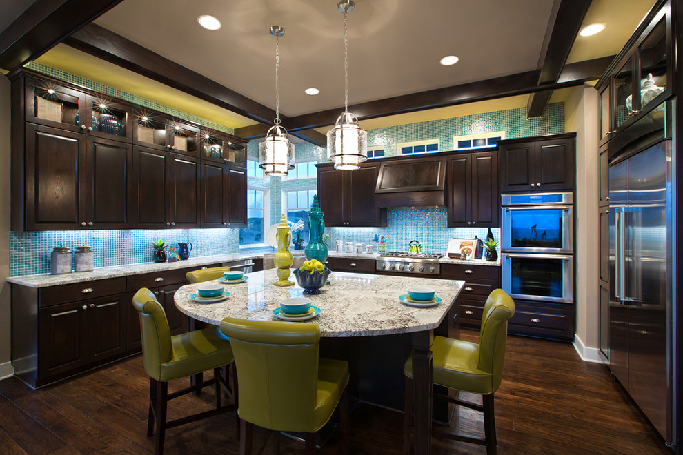 Elegant kitchen photo in Austin with raised-panel cabinets, dark wood cabinets, blue backsplash and stainless steel appliances