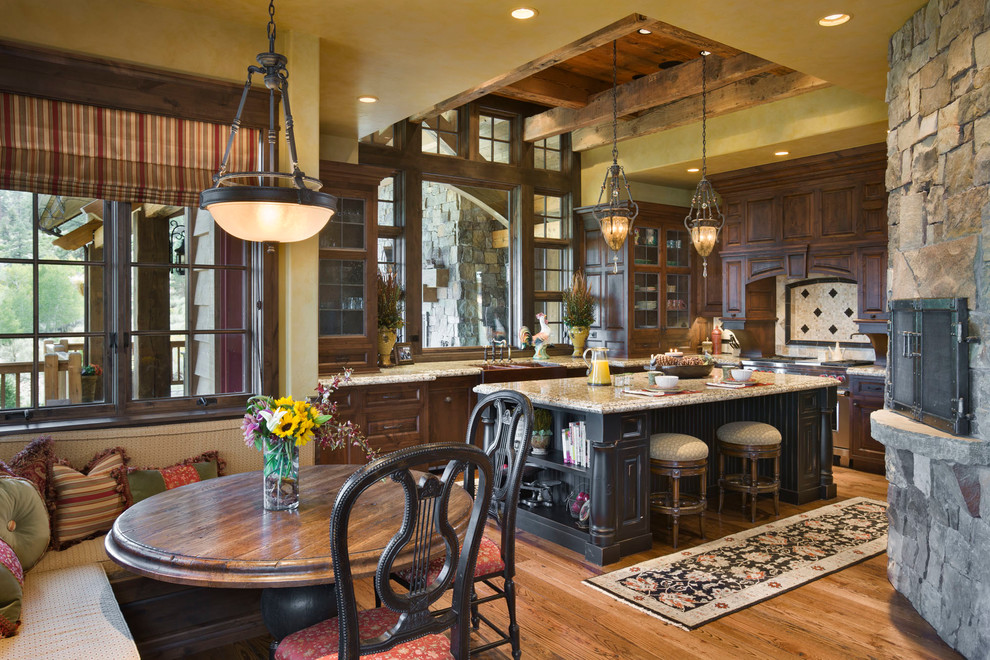 Example of a mountain style l-shaped eat-in kitchen design in Other with a farmhouse sink, recessed-panel cabinets, multicolored backsplash, mosaic tile backsplash, stainless steel appliances and dark wood cabinets