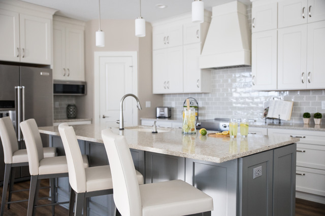 Eat-in kitchen - large transitional l-shaped vinyl floor and brown floor eat-in kitchen idea in Other with an undermount sink, recessed-panel cabinets, white cabinets, quartz countertops, gray backsplash, subway tile backsplash, stainless steel appliances, an island and multicolored countertops