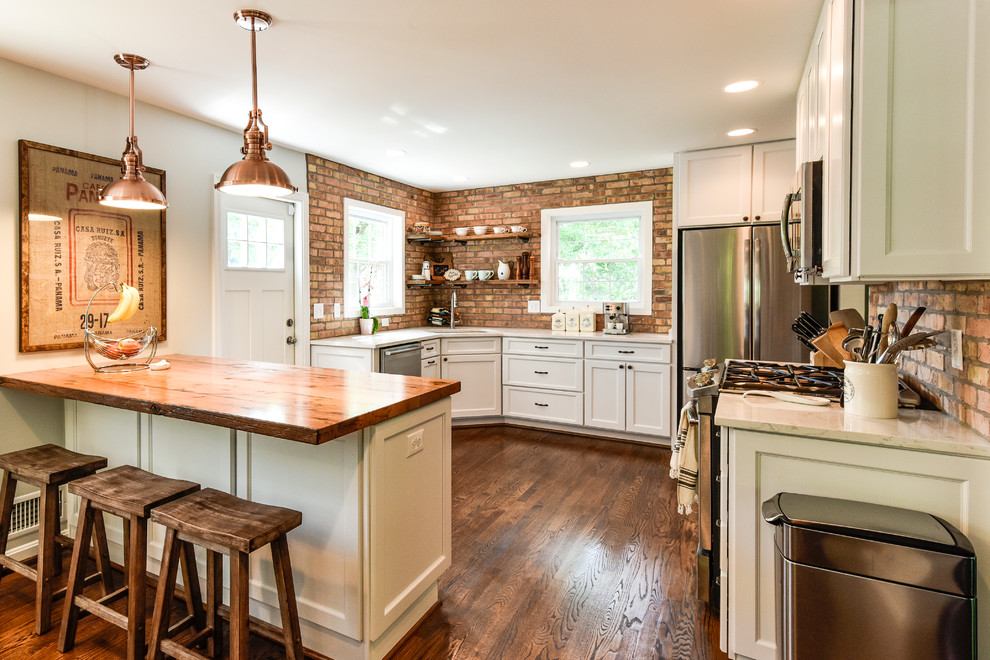 Example of a mid-sized country u-shaped dark wood floor and brown floor enclosed kitchen design in DC Metro with an undermount sink, shaker cabinets, white cabinets, wood countertops, red backsplash, brick backsplash, stainless steel appliances and a peninsula
