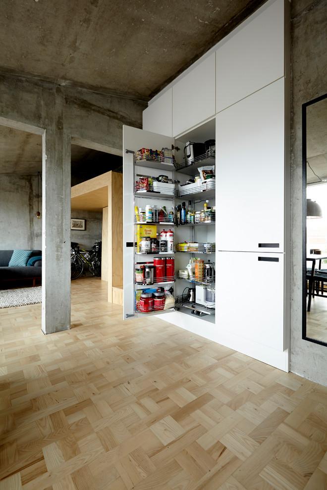 Offene, Große Industrial Küche ohne Insel mit weißen Schränken und braunem Holzboden in Esbjerg