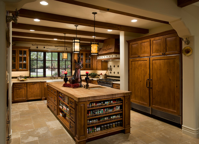 Large tuscan u-shaped limestone floor and beige floor kitchen photo in Phoenix with a farmhouse sink, recessed-panel cabinets, medium tone wood cabinets, multicolored backsplash, paneled appliances, an island, limestone backsplash and wood countertops