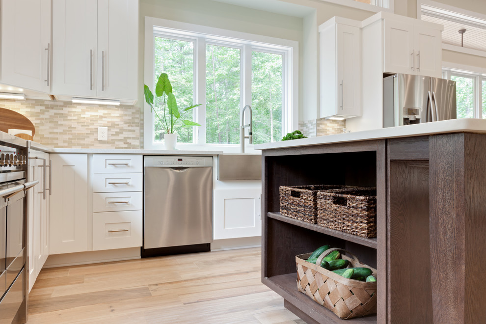 Huge trendy u-shaped porcelain tile and beige floor eat-in kitchen photo in Atlanta with a farmhouse sink, shaker cabinets, white cabinets, quartz countertops, beige backsplash, glass tile backsplash, stainless steel appliances, an island and white countertops