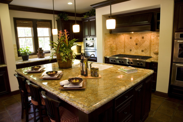 Kashimier Gold granite countertop with travertine back splashes traditional-kitchen
