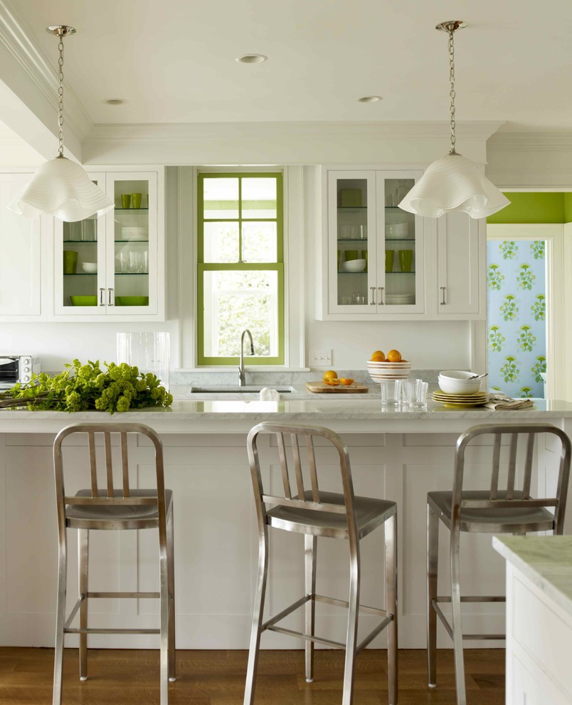 Example of a transitional kitchen design in New York with glass-front cabinets, marble countertops, an undermount sink and white cabinets