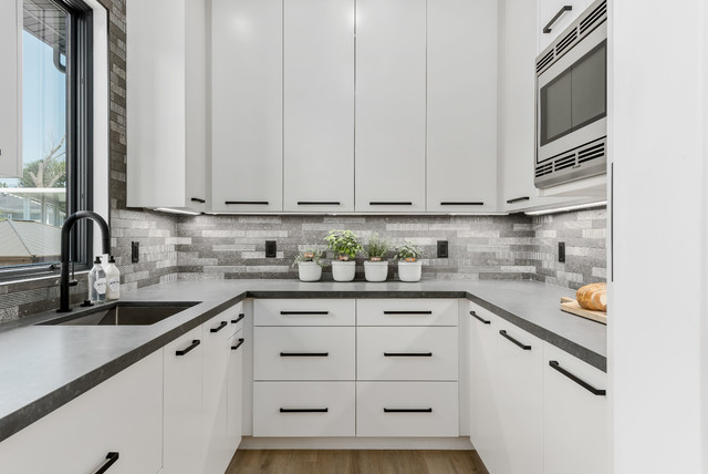 Large trendy l-shaped porcelain floor and beige floor eat-in kitchen photo in Salt Lake City with a farmhouse sink, flat-panel cabinets, white cabinets, quartzite countertops, gray backsplash, stone tile backsplash, stainless steel appliances, an island and gray countertops