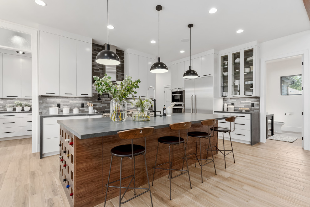 Inspiration for a large contemporary l-shaped porcelain tile and beige floor eat-in kitchen remodel in Salt Lake City with a farmhouse sink, flat-panel cabinets, white cabinets, quartzite countertops, gray backsplash, stone tile backsplash, stainless steel appliances, an island and gray countertops