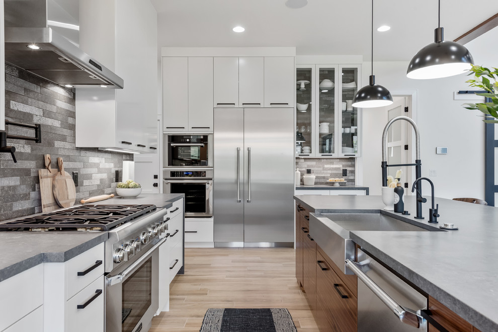 Eat-in kitchen - large contemporary l-shaped porcelain tile and beige floor eat-in kitchen idea in Salt Lake City with a farmhouse sink, flat-panel cabinets, white cabinets, quartzite countertops, gray backsplash, stone tile backsplash, stainless steel appliances, an island and gray countertops