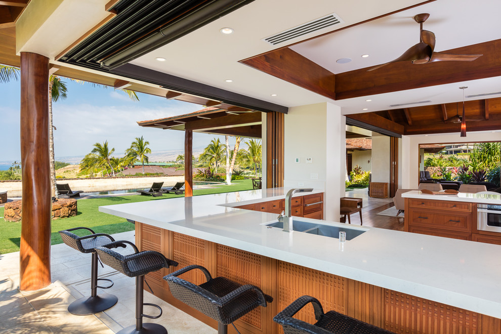 Open concept kitchen - large tropical l-shaped limestone floor open concept kitchen idea in Hawaii with a double-bowl sink, recessed-panel cabinets, medium tone wood cabinets, quartz countertops, stainless steel appliances and a peninsula