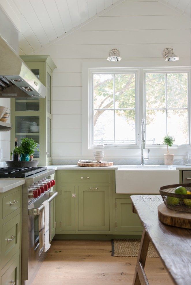 Inspiration for a small country u-shaped light wood floor eat-in kitchen remodel in New York with a farmhouse sink, recessed-panel cabinets, green cabinets, marble countertops, white backsplash, stainless steel appliances and no island