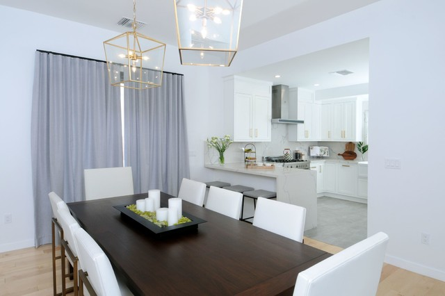 Inspiration for a mid-sized transitional l-shaped porcelain floor and gray floor eat-in kitchen remodel in Los Angeles with a farmhouse sink, shaker cabinets, white cabinets, quartz countertops, white backsplash, stainless steel appliances and a peninsula