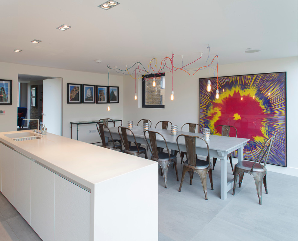 Eat-in kitchen - contemporary galley eat-in kitchen idea in London with an integrated sink, flat-panel cabinets, white cabinets and solid surface countertops