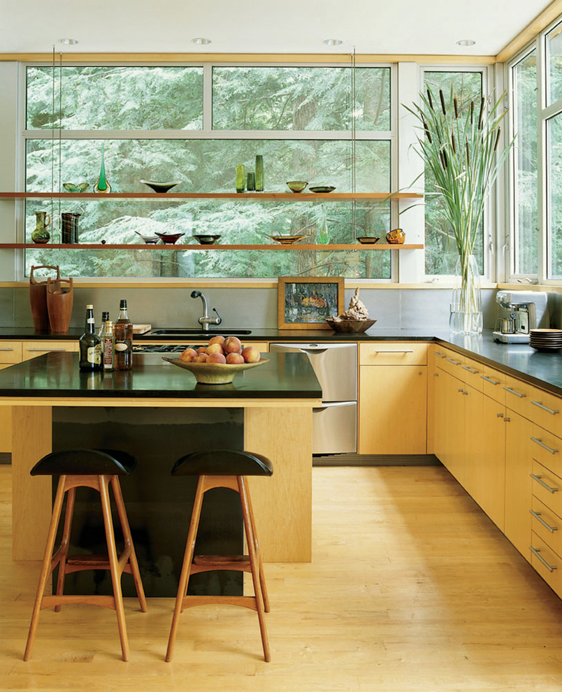 Example of a trendy l-shaped light wood floor and beige floor kitchen design in New York with flat-panel cabinets, light wood cabinets, window backsplash, stainless steel appliances, an island and black countertops