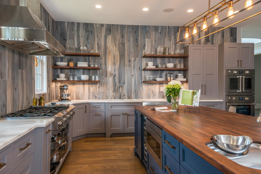 Example of a large transitional l-shaped medium tone wood floor and brown floor kitchen design in Other with an undermount sink, shaker cabinets, gray cabinets, wood countertops, gray backsplash, stainless steel appliances, an island and brown countertops