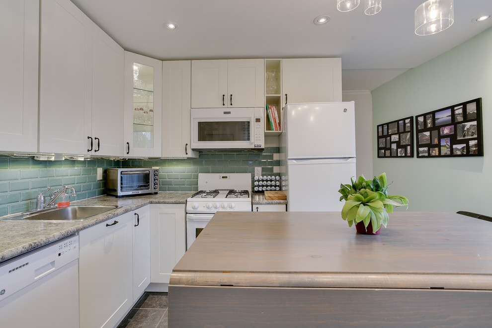 Small transitional l-shaped ceramic tile eat-in kitchen photo in Toronto with a single-bowl sink, shaker cabinets, yellow cabinets, laminate countertops, green backsplash, glass tile backsplash, white appliances and an island