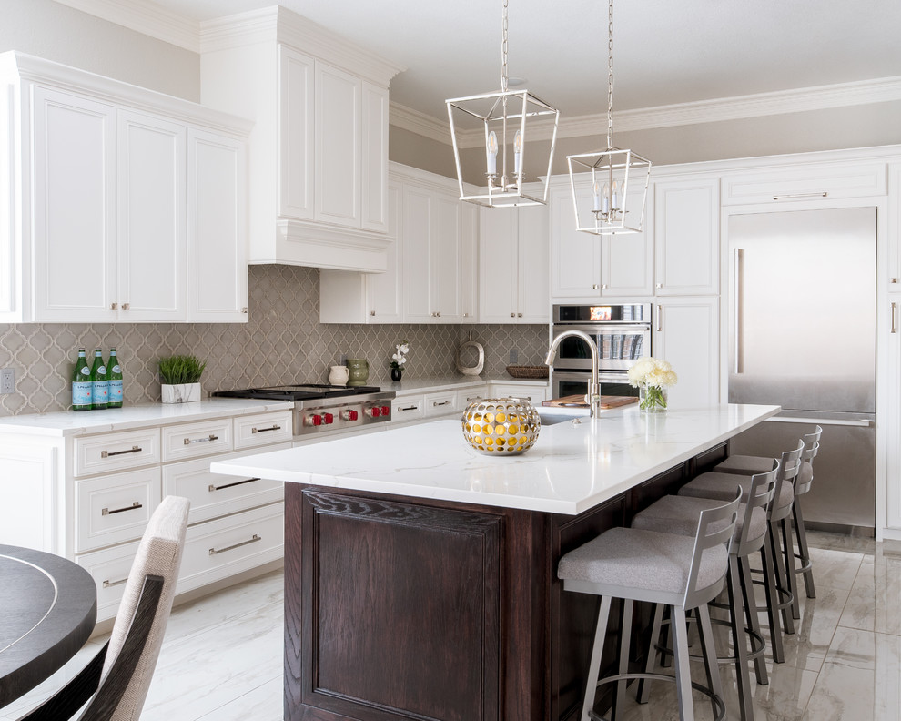 Eat-in kitchen - mid-sized traditional l-shaped porcelain tile and white floor eat-in kitchen idea in Dallas with an undermount sink, shaker cabinets, white cabinets, quartz countertops, gray backsplash, porcelain backsplash, stainless steel appliances, an island and white countertops
