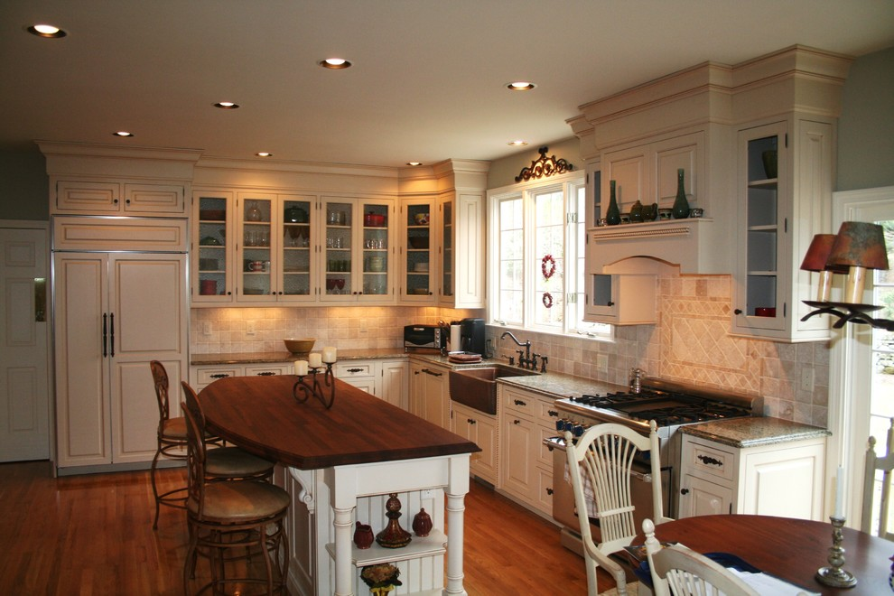 Example of a classic kitchen design in Boston with glass-front cabinets, a farmhouse sink, wood countertops and paneled appliances